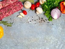 Raw meat on a sheet of tin. Nearby spices, condiments and vegetables. stock image