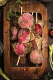 Raw meat skewers with fresh seasoning crust in rustic wooden plate, top view Royalty Free Stock Image