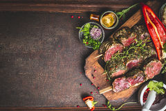 Raw Meat skewers and vegetables for grill on dark wooden background, top view Stock Photography