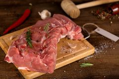 Raw meat slices on the board. Raw cut meat on a wooden board. Pork chunks for chops with pepper, salt, garlic and thyme Stock Image