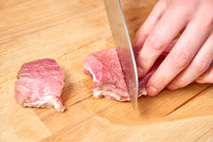 Raw meat slices cutted with knife on wooden board Royalty Free Stock Photo