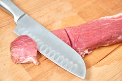 Raw meat slices cutted with knife on wooden board Stock Image