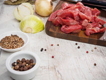 Raw meat slices on cutting board with pepper and. Onion.Horizontal image Royalty Free Stock Photos