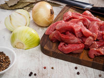 Raw meat slices on cutting board with pepper and. Onion.Horizontal image Royalty Free Stock Image