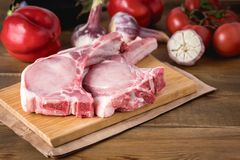 Raw Meat Slices on a Wooden Rustic Background with Fresh Organic Vegetables Garlic,Tomatoes Pepper for Cooking Kitchen ideas Lunch. Dinner Copy Space Stock Photos