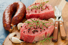 Raw meat with smoked sausage, pepper and garlic on wooden board Stock Photos
