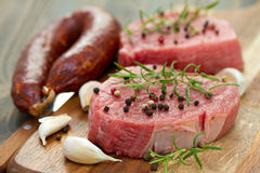 Raw meat with smoked sausage, pepper and garlic on wooden board Royalty Free Stock Photo