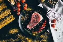 Raw meat with spices, cherry tomatoes, pepper, onion and olives, lying on black background and white napkin. Cooking. Delicious dinner for party or a romantic Royalty Free Stock Image