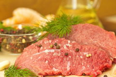 Raw meat with spices and vegetables ready for cooking. Piece of raw meat with spices and vegetables ready for cooking Stock Images