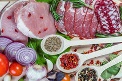 Raw meat, spices and vegetables. On rustic wooden board Royalty Free Stock Images
