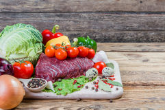 Raw meat, spices and vegetables. On rustic wooden board Stock Photos