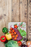 Raw meat, spices and vegetables. On rustic wooden board Stock Photo