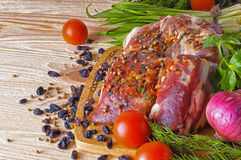 Raw meat, spices and vegetables. Raw meat, surrounded by vegetables and spices Royalty Free Stock Photo
