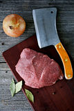 Raw meat steak. And a butcher axe on the wooden table Royalty Free Stock Images