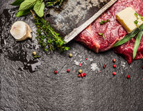 Raw meat Steak with butter, fresh seasonings and  blade of old knife on dark stone background. Top view, horizontal Royalty Free Stock Images