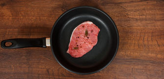 Raw meat steak on cast iron frying pan on the brown wooden table background. rustic kitchen table with copy space Stock Images