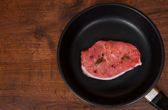 Raw meat steak on cast iron frying pan on the brown wooden table background. rustic kitchen table with copy space Royalty Free Stock Photography