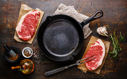 Raw meat Steak with condiments around frying pan. Raw fresh meat Steak Striploin for two with condiments around iron frying pan Royalty Free Stock Photo