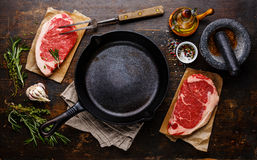 Raw meat Steak with condiments around pan. Raw fresh meat Steak Striploin for two with condiments around iron frying pan Royalty Free Stock Images