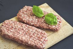 Raw meat steak cutlets for burger. Raw meat steak cutlet for burger   with fresh  basil oand ingredients for cooking. on black slate Stock Images