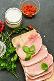 Raw meat steak cutlet and ingredients for cooking. Raw meat steak cutlet   with fresh  basil and ingredients for cooking.  chili peppers ,parsley, rosmary   and Stock Images