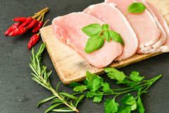 Raw meat steak cutlet and ingredients for cooking. Raw meat steak cutlet   with fresh  basil and ingredients for cooking.  chili peppers ,parsley, rosmary   and Stock Photo
