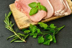 Raw meat steak cutlet and ingredients for cooking. Raw meat steak cutlet   with fresh  basil and ingredients for cooking.  chili peppers ,parsley, rosmary   and Royalty Free Stock Images
