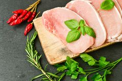 Raw meat steak cutlet and ingredients for cooking. Raw meat steak cutlet   with fresh  basil and ingredients for cooking.  chili peppers ,parsley, rosmary   and Royalty Free Stock Photos