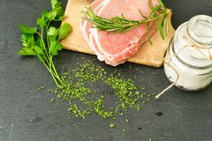 Raw meat steak cutlet and ingredients for cooking. Raw meat steak cutlet   with fresh  basil and ingredients for cooking.  chili peppers ,parsley, rosmary   and Royalty Free Stock Photo