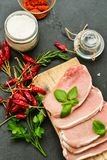 Raw meat steak cutlet and ingredients for cooking. Raw meat steak cutlet   with fresh  basil and ingredients for cooking.  chili peppers ,parsley  and salt on Stock Images