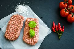 Raw meat steak cutlets for burger. Raw meat steak cutlet for burger   with fresh  basil and ingredients for cooking Tomatoes, black pepper , red chili peppers Royalty Free Stock Image