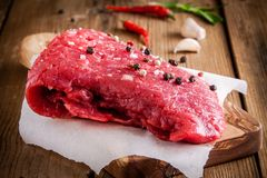 Raw meat steak on a cutting board with garlic and pepper Stock Image