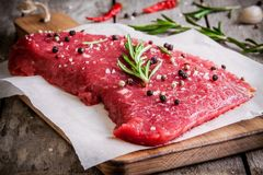 Raw meat steak on a cutting board with rosemary and red pepper. Fresh raw meat steak on a cutting board with rosemary and pepper on rustic background Royalty Free Stock Image
