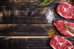 Raw meat steak on dark wooden background ready to roasting Royalty Free Stock Photo