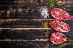 Raw meat steak on dark wooden background ready to roasting Stock Photos