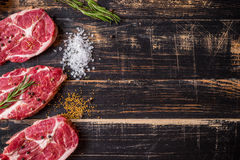 Raw meat steak on dark wooden background ready to roasting Royalty Free Stock Photography