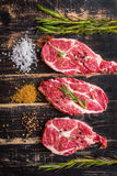 Raw meat steak on dark wooden background ready to roasting Royalty Free Stock Photos