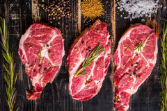 Raw meat steak on dark wooden background ready to roasting stock photography