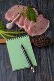 Raw meat steak on dark wooden board. recipe Stock Photography