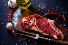 Raw meat steak entrecote on the cutting board with spice on the Royalty Free Stock Photo