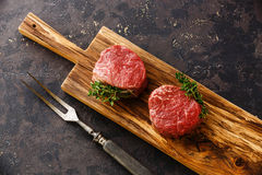 Raw meat Steak filet mignon and meat fork. Raw fresh marbled meat Steak filet mignon and meat fork on black background Stock Image