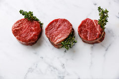 Raw meat Steak filet mignon and thyme. Raw fresh marbled meat Steak filet mignon and thyme on white marble background Royalty Free Stock Images