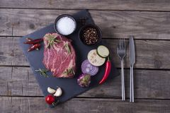 Raw meat steak from marble beef with vegetables and spices on the stone plate. Top view.  Royalty Free Stock Photography