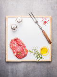 Raw meat Steak with oil, spices and meat fork on  white kitchen tray on gray stone background. Top view, frame Stock Photography