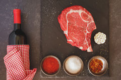 Raw meat steak rib eye with a bottle of wine Royalty Free Stock Images