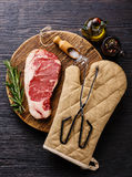 Raw meat steak with salt and pepper and tongs Royalty Free Stock Photo