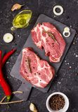 Raw meat steak with seasonings on black stone background. Steak ready for cooking. Barbecue concept. Ingredients for Royalty Free Stock Photography