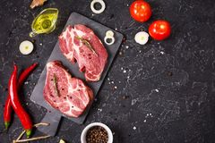 Raw meat steak with seasonings on black stone background. Space for text. Steak ready for cooking. Barbecue concept Stock Image
