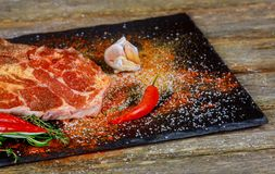 Raw meat steak with seasonings on black stone background. Steak ready for cooking. Ingredients for meat roasting. Raw meat steak with seasonings on black stone Royalty Free Stock Photos