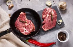 Raw meat steak with seasonings on concrete background. Steak ready for cooking. Ingredients for meat roasting. Top view Stock Photos
